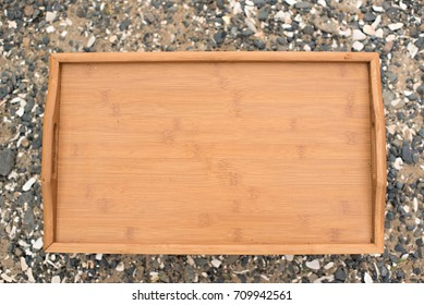 Wooden tray on a background sea pebbles. The view from the top