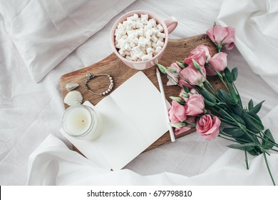 Wooden tray with paper sketchbook, marshmallows, candle and spring flowers on clean white bedding. Good morning concept.
