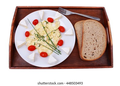 A wooden tray with a plate of scrambled eggs, cheese, bread, cherry tomatoes and chives on a white background