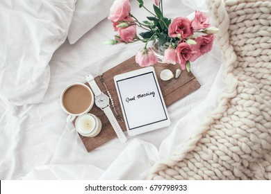 Wooden tray with tablet, coffee and spring flowers on clean white bedding. Good morning concept.