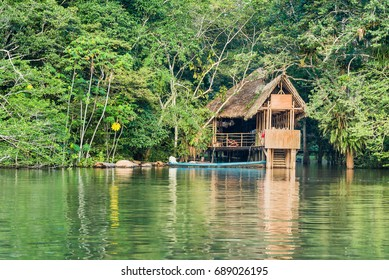 Wooden treehouse style cabin in the jungle with long blue canoe
