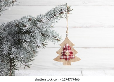 Wooden tree-shaped Christmas toy hanging on snowy fir branch, holiday decoration