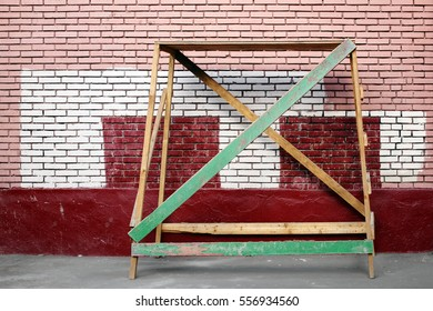 A wooden trestle on the background of a brick wall which is painted in different colors. Russia, Moscow, August 2016.