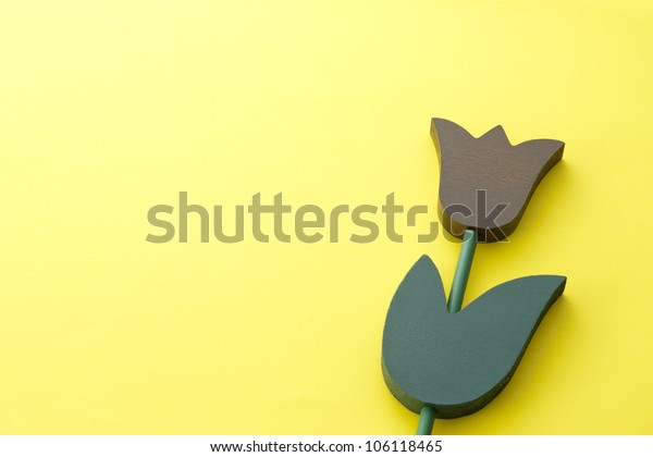 wooden tulips on yellow background