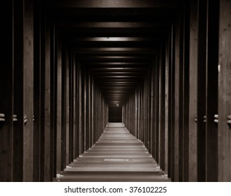 wooden tunnel lit by lamps black and white