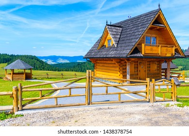 Wooden typical mountain house on green meadow in Tatra Mountains on sunny summer day, Poland