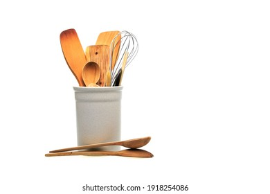 Wooden utensils for cooking are in a white glass. Kitchen spoons, scoops, forks isolated on white background. Scandinavian style in the interior of the kitchen.