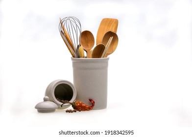 Wooden utensils for cooking in a white glass and red hot pepper. Kitchen spoons, scoops, forks isolated on white background. Scandinavian style in the interior of the kitchen.