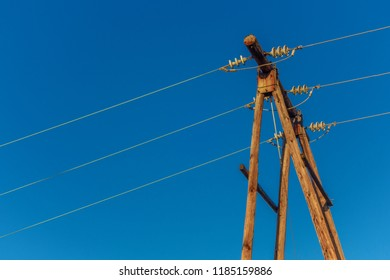 Wooden utility pole with power lines against a bright blue sky with empty space
