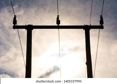 Wooden utility poles with electricity wires on a cloudy sky
