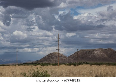 Wooden utility post with power lines in desert hills landscape/View of Wood Electricity Pole and Energy Lines in Dry Rural Region/Utility pole of wood with power lines in countryside