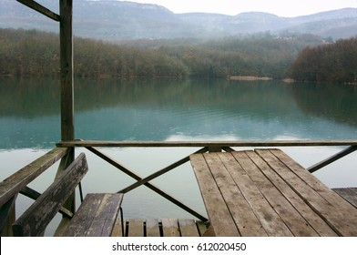 Wooden veranda with table and benches on mountain lake at rainy weather.