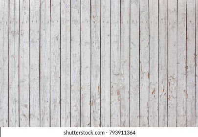 Wooden vertical boards with flakes of exfoliated sulfur paint on the surface. Rustic vintage wooden rural fence.