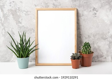 Wooden vertical frame with white blank card, and green houseplants flowers in pot on table on gray concrete wall background. Mockup Template for your design, text.