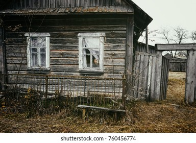 wooden village house and a granny in the window