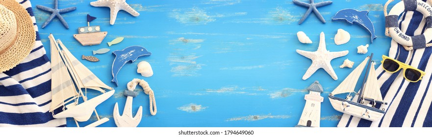 wooden vintage boat, towel and sea shells over blue background