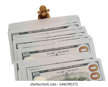 Wooden Vintage Monkey Figurine Supporting A Fanned Out Stack Of Hundred Dollar Bills Over A White Background