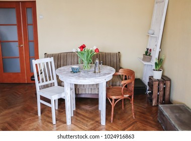 Wooden vintage Old round white table and old chairs, coffee pot and bouquet of tulips