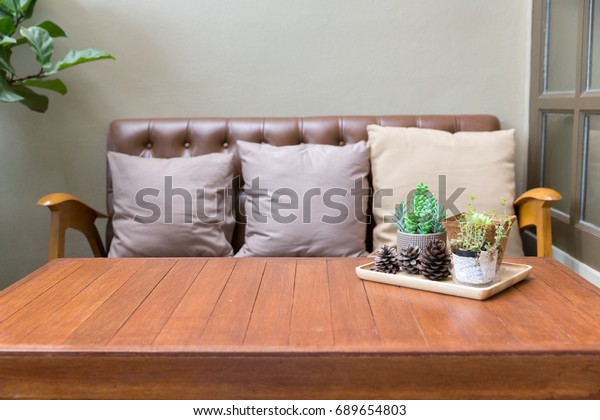 Wooden vintage style table and sofa with pillow and decoration tree. Concept of vintage style decoration living room