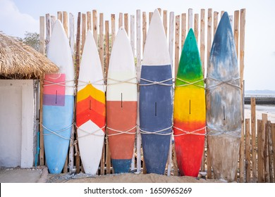 Wooden vintage Surfboard and Bamboo fence stands in the sand