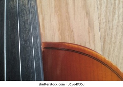 Wooden violin part on black background, macro.