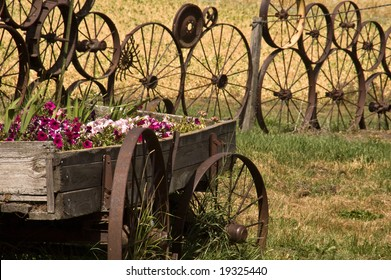Wooden wagon containing flowers, with fence made of wheels in the background