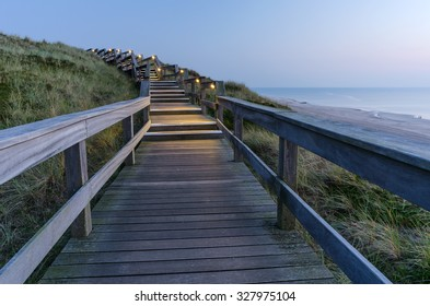 A wooden walking path at night near Wenningstedt on the island of Sylt, Schleswig-Holstein, Germany
