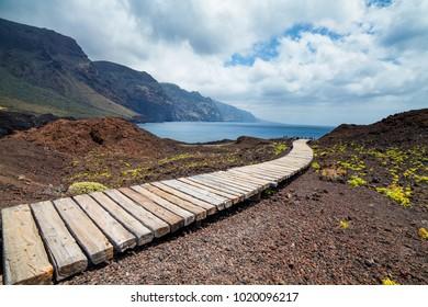 Wooden walking path at Punta de Tena. Los Gigantes rocks and ocean view at sunset light. Tenerife, Canarias, Spain.