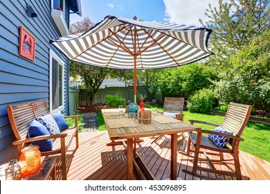 Wooden walkout deck in the backyard garden of blue siding house. Furnished with patio table set with umbrella