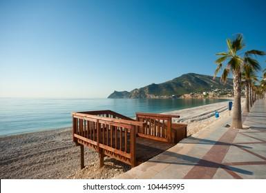 Wooden walkway to access a sunny Mediterranean beach