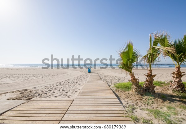 wooden walkway to Almadraba Beach in Benicassim, Castellon, Valencia, Spain, Europe. Lonely golden sand, palm trees, trash can, blue clear sky and Mediterranean Sea