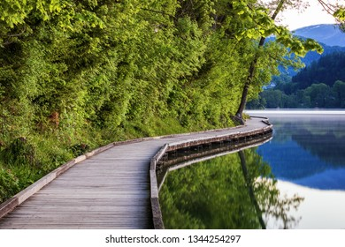Wooden walkway around the lake Bled with mountains and houses on the background. Beautiful Slovenian Nature. Bled, Slovenia, Europe.