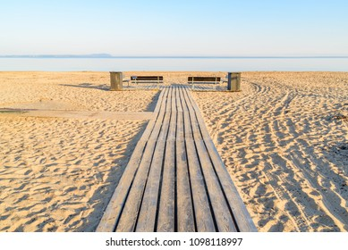 Wooden walkway at a beach, with two empty benches and trash bins on the sides. Windless sea under the horizon on a sunny morning before the bathers arrive. Angelholm in Sweden.