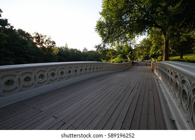 Wooden walkway of Bow bridge under the shade and trees at Central Park