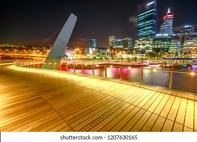 Wooden walkway of Elizabeth Quay pedestrian bridge illuminated by night at Elizabeth Quay marina, a new tourist attraction in Perth, Western Australia. Esplanade on background. Night scene.