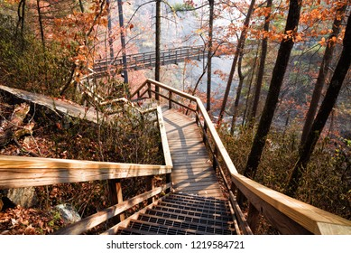 Wooden walkway leading towards a suspension bridge that crosses over the Tallulah River in Tallulah Gorge State Park in Georgia USA. Autumn leaf color.