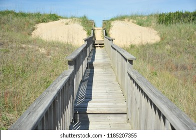 A wooden walkway leads to the beach