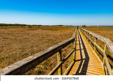 Wooden Walkway at Newtown Creek, Isle of Wight, England. The boardwalk crosses reed beds and marshes to Newtown Quay, with the Solent and New Forest in the distance. Copy space.