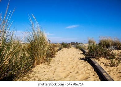 Wooden walkway over the sand dunes to the beach. Beach pathway in Huelva Beach, inside a nature reserve in Andalusia, Spain