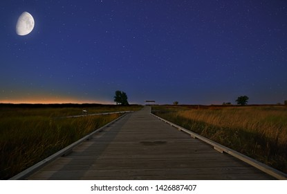 The wooden walkway through the grassland at Headlands Beach State Park, Ohio under a waxing gibbous moon. This walkway leads to Headlands Beach at Lake Erie.