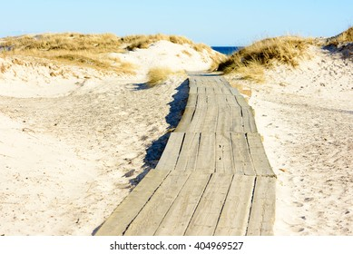Wooden walkway or wheelchair trail on sandy beach going between sand dunes down towards the sea. A sunny and fine day at the beach. No person visible. Sandhammaren, Sweden.