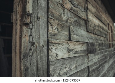 Wooden wall of an abandoned old house. In place of the door is fixed a thick chain. The chain in focus in the foreground the wall fades into the background in a blur