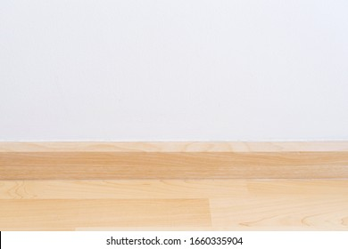 Wooden wall base skirting, finishing material with wood laminate floor and white mortar wall. Empty room with white wall and wooden floor new clean modern design.