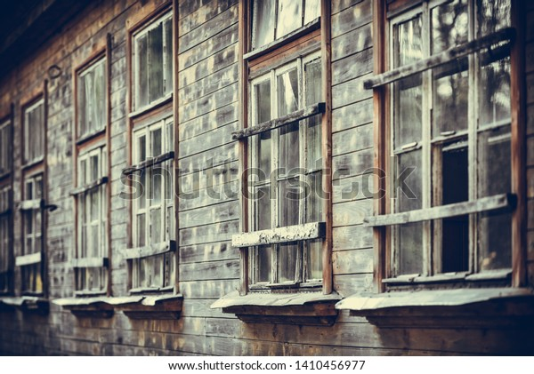 Wooden wall close-up and old wooden windows on the facade of an old house