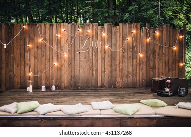 Wooden wall decorated by electric lamps and Love sign. Vintage suitcases and pillows on floor. Wedding. Reception. Lounge zone.