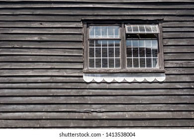 Wooden wall and two classic windows of the old house