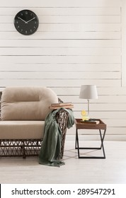 wooden wall and the wicker sofa with clock