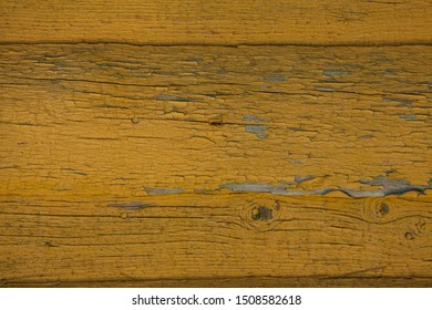 Wooden wall with yellow paint. Photo background with cracked yellow paint on the wall