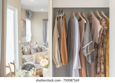 wooden wardrobe with clothes hanging on rail, interior design concept
