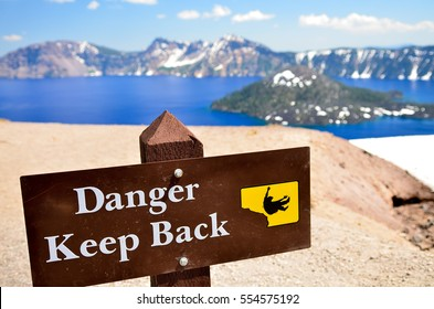 A wooden warning sign with white text that read danger keep back and with illustration in yellow of a man falling off, taken near a cliff. In the background are crater lake and wizard island.
